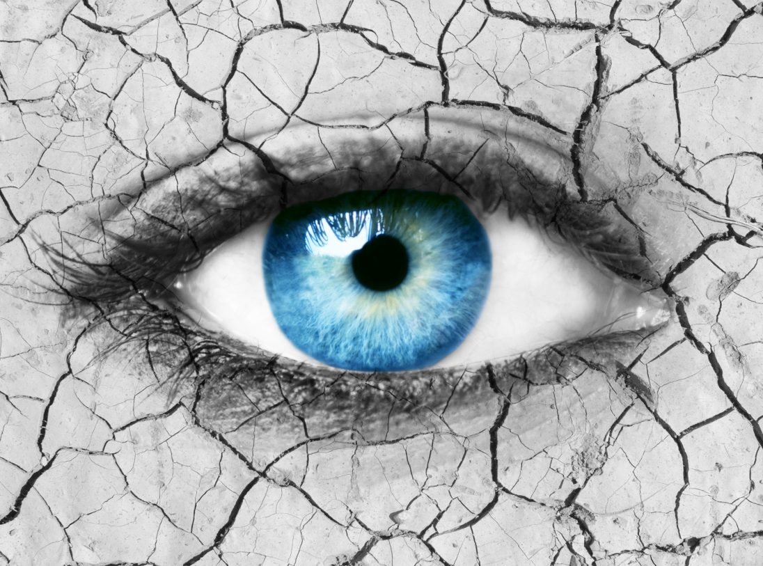 Global warming conceptual image with blue eye and cracked earth texture